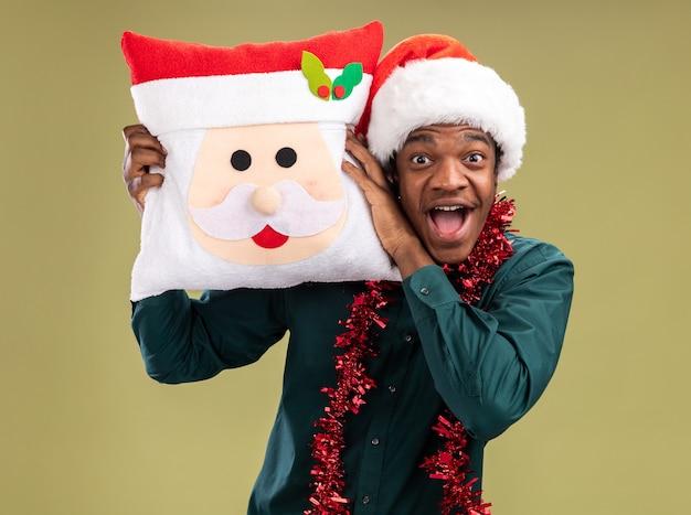 Gelukkig en opgewonden afro-amerikaanse man in kerstmuts met slinger kerst kussen houden kijken camera staande over groene achtergrond Gratis Foto