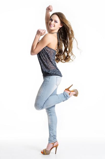 Gelukkig en vreugde mooi meisje in mode stijlvolle jeans - geïsoleerd op wit. mannequin poseren in de studio Gratis Foto