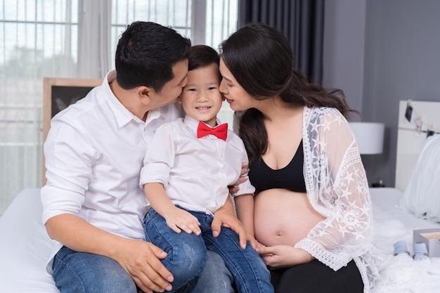 Gelukkig familieconcept, zwangere moeder en vader kussende jongen jongen Premium Foto