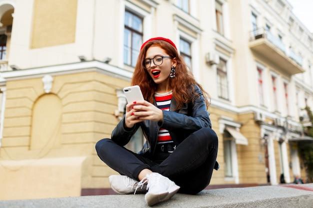 Gelukkig fantastische gember vrouw in stijlvolle rode baret in de straat met behulp van haar smartphone Gratis Foto