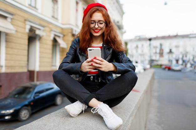 Gelukkig fantastische gember vrouw in stijlvolle rode baret in de straat met smartphone Gratis Foto