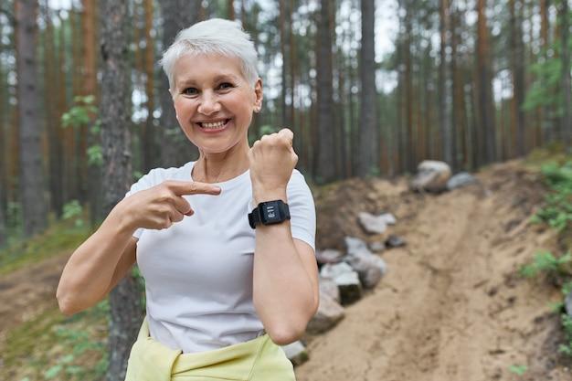 Gelukkig fit gepensioneerde vrouw in activewear glimlachend in grote lijnen wijzend op weergave van slimme pols horloge Gratis Foto
