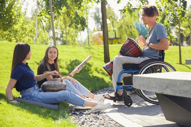 Gelukkig gehandicapte man in een rolstoel tijd doorbrengen met vrienden die live instrumentale muziek buiten spelen. Gratis Foto
