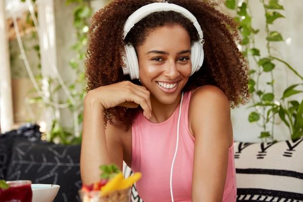 Gelukkig gemengd ras tienermeisje met krullend kapsel blij om te luisteren naar muziek of radio in koptelefoon, heeft langverwachte vakanties, zit op comfortabele bank met dessert. vrouwelijke blogger houdt van melodie Gratis Foto