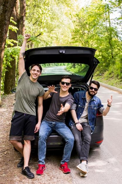 Gelukkig gezelschap van jonge jongens zitten in de kofferbak in reizen Gratis Foto