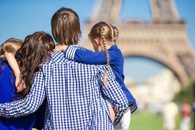 Gelukkig gezin met twee kinderen in de buurt van de eiffeltoren op vakantie in parijs Premium Foto