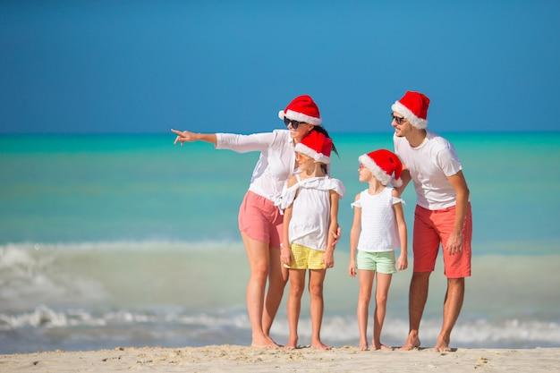Gelukkig gezin met twee kinderen in santa hat op zomervakantie Premium Foto