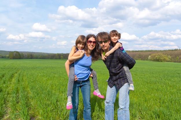 Gelukkig gezin met twee kinderen op groen veld Premium Foto
