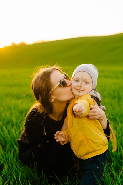 Gelukkig gezin met zoon buitenshuis. jonge ouders lopen met kind op zomer veld Premium Foto