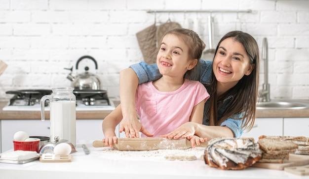 Gelukkig gezin. moeder en dochter bereiden gebak in de keuken. Premium Foto
