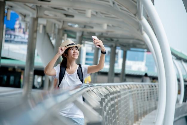 Gelukkig glimlachend aziatisch studentenmeisje met rugzak bij stadsachtergrond Gratis Foto