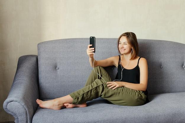 Gelukkig glimlachend meisje die aan muziek in oortelefoons luisteren terwijl het nemen van een selfie op een smartphone, die vrije tijd met plezier doorbrengen aan de bank, thuis Premium Foto