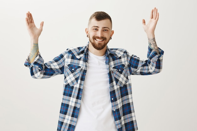 Gelukkig glimlachende man handen opsteken verheugd, goed nieuws ontvangen Gratis Foto