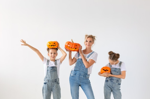 Gelukkig halloween en vakantieconcept - een moeder en haar dochters met pompoenen. gelukkig gezin Premium Foto