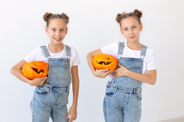 Gelukkig halloween, vakantie en jeugdconcept - schattige kleine tweelingzusjes meisjes met een pompoenen jack-o'-lantern plezier terwijl ze tijd binnenshuis doorbrengen. Premium Foto