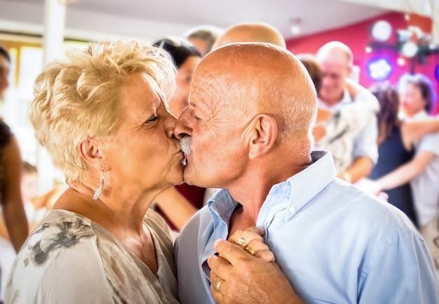 Gelukkig hoger gepensioneerd paar dat pret bij het dansen bij de vieringspartij van het restauranthuwelijk heeft Premium Foto