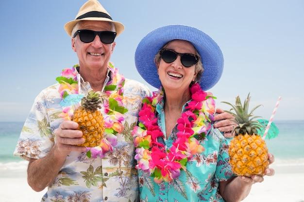 Gelukkig hoger paar dat een slinger draagt en ananascocktail houdt Premium Foto