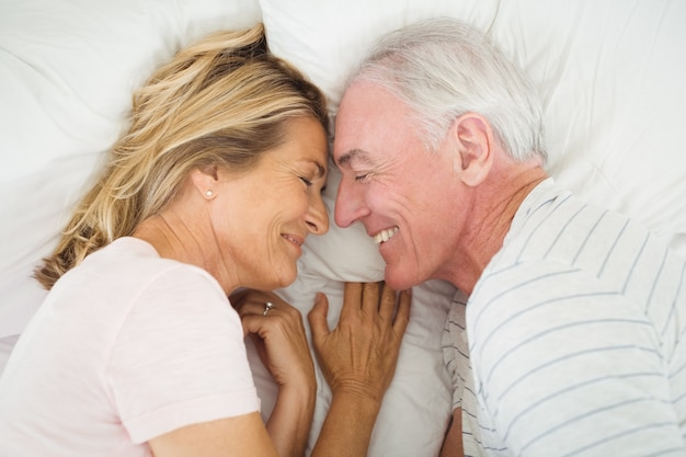 Gelukkig hoger paar dat op bed ligt Premium Foto