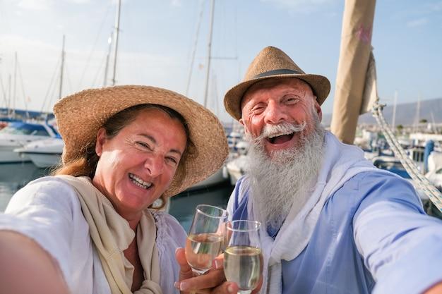 Gelukkig hoger paar dat selfie doet, toejuichend met champagne op een zeilboot tijdens verjaardagsvakantie Premium Foto
