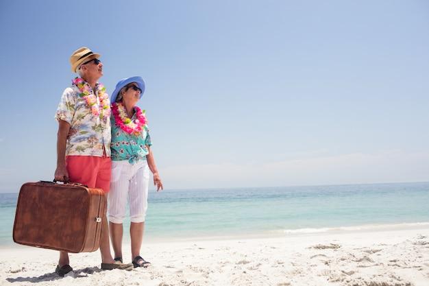 Gelukkig hoger paar dat zich op strand met koffer bevindt Premium Foto