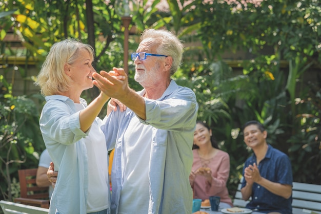Gelukkig hoger paar die na ontbijt in de ochtend met hun familie thuis tuin dansen Premium Foto
