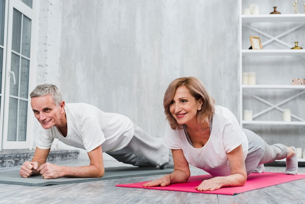 Gelukkig hoger paar die yogaoefening thuis doen Gratis Foto