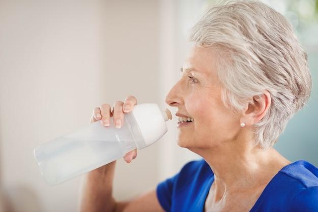 Gelukkig hoger vrouwen drinkwater na een training Premium Foto