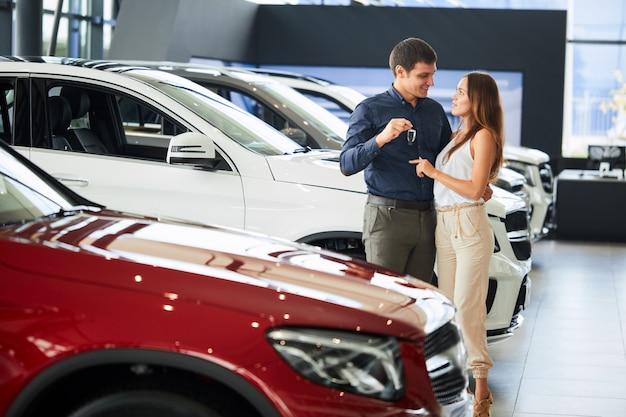 Gelukkig houdend van paar die dichtbij hun nieuwe luxeauto bij het handel drijven omhelzen. Premium Foto