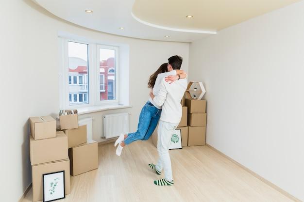 Gelukkig houdend van paar met kartondozen in nieuw huis bij bewegende dag Gratis Foto