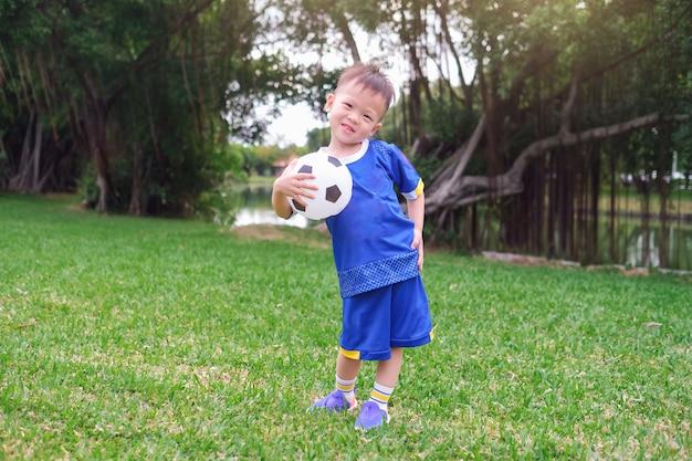 Gelukkig houdt weinig voetballer in eenvormig voetbal voetbal Premium Foto