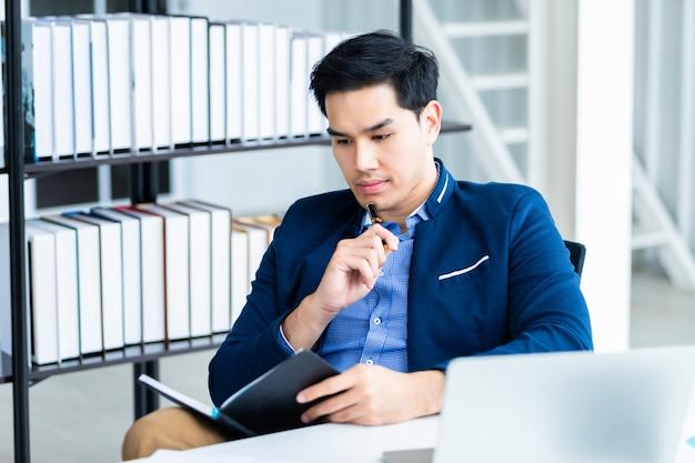 Gelukkig humeur een vrolijk van aziatische jonge zakenman die werkt met het maken van aantekeningen in een notebook en laptopcomputer in de kantoorruimte. Premium Foto