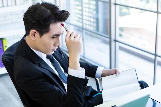 Gelukkig humeur een vrolijke van aziatische jonge zakenman ideeën hebben, noteer het succesvolle businessplan in een notebook en computer op houten tafel achtergrond in kantoor. Premium Foto