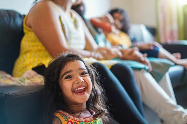 Gelukkig indisch meisje kind sari jurk zittend op de bank met ouders thuis dragen Premium Foto