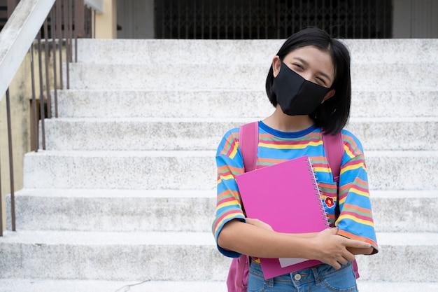 Gelukkig jong aziatisch meisje draagt masker en houdt boek op school Premium Foto