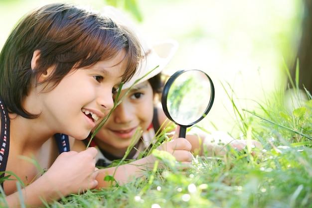 Gelukkig jong geitje die aard met vergrootglas onderzoeken Premium Foto