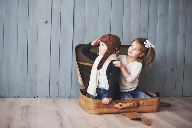 Gelukkig jong geitje in proefhoed en meisje het spelen met oude koffer. childhood. fantasie, verbeelding. reizen Premium Foto