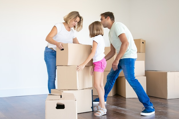 Gelukkig jong gezin met kartonnen dozen verhuizen naar een nieuw huis of appartement Gratis Foto