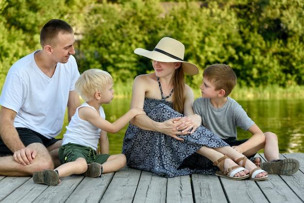 Gelukkig jong gezin, vader moeder en twee zoontjes zitten op de rivier pier Premium Foto