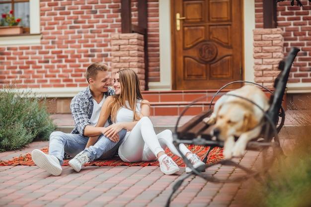 Gelukkig jong koppel genieten van elkaar en zitten aan het deken tapijt voor het huis. de hond slaapt op de bank Premium Foto