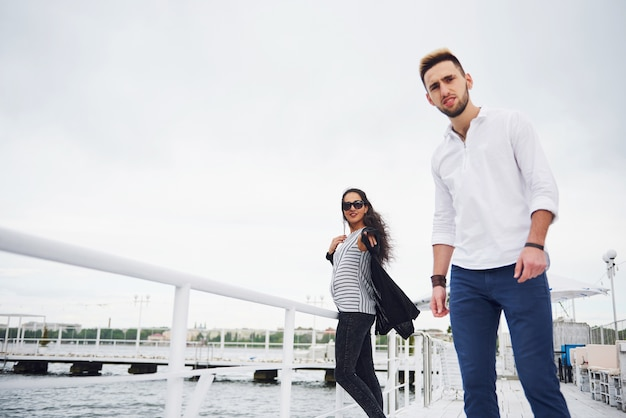 Gelukkig jong koppel in stijlvolle merkkleding, staande op de pier in het water. Gratis Foto
