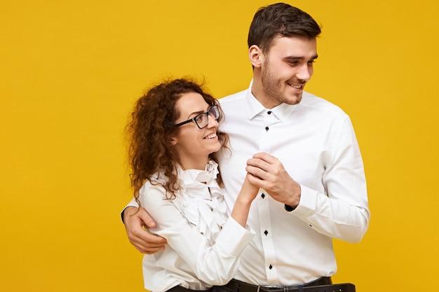 Gelukkig jong koppel verliefd genieten van leuke tijd samen op eerste date. aantrekkelijke man en vrouw dansen, met vrolijke blikken, witte shirts dragen. saamhorigheid, familie en relaties concept Gratis Foto