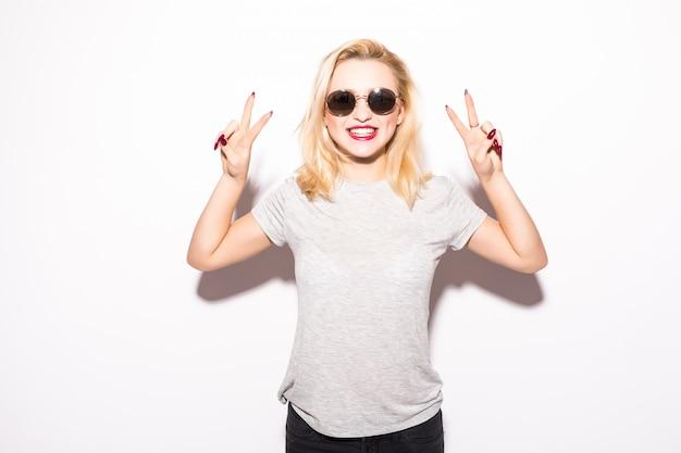 Gelukkig jong meisje in zonnebril die vredesteken tonen Gratis Foto
