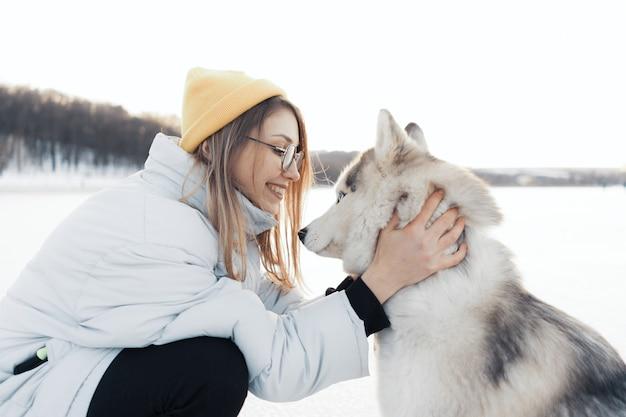 Gelukkig jong meisje spelen met siberische husky hond in winter park Gratis Foto