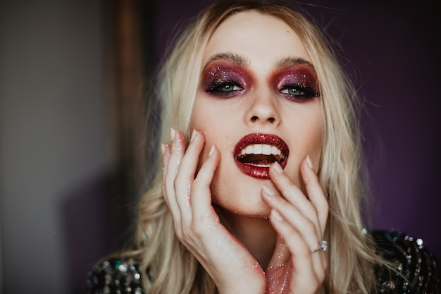 Gelukkig jong model met trendy make-up die goede emoties uitdrukt. binnenfoto van bevallige blanke vrouw met blond golvend haar. Gratis Foto