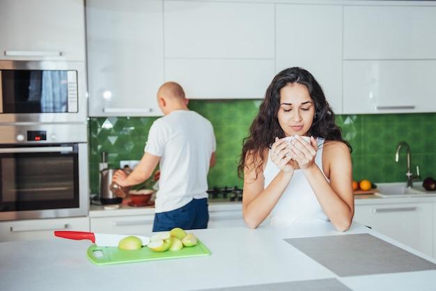 Gelukkig jong paar dat koffie in de keuken heeft Premium Foto
