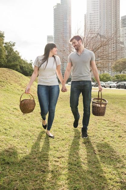 Gelukkig jong paar dat met rieten mand in het park loopt Gratis Foto