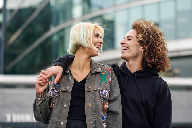 Gelukkig jong paar dat op stedelijke achtergrond lacht Premium Foto