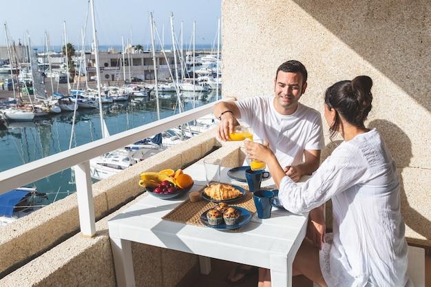 Gelukkig jong paar dat van ontbijt op het terras geniet Premium Foto