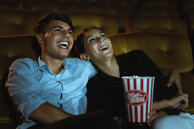 Gelukkig jong paar die komische film kijken in het bioscooptheater Premium Foto
