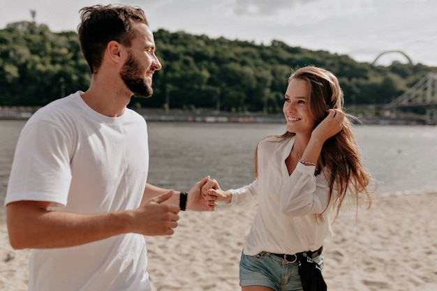 Gelukkig jong paar verliefd en glimlachen terwijl ze op het strand bij het meer liggen Gratis Foto